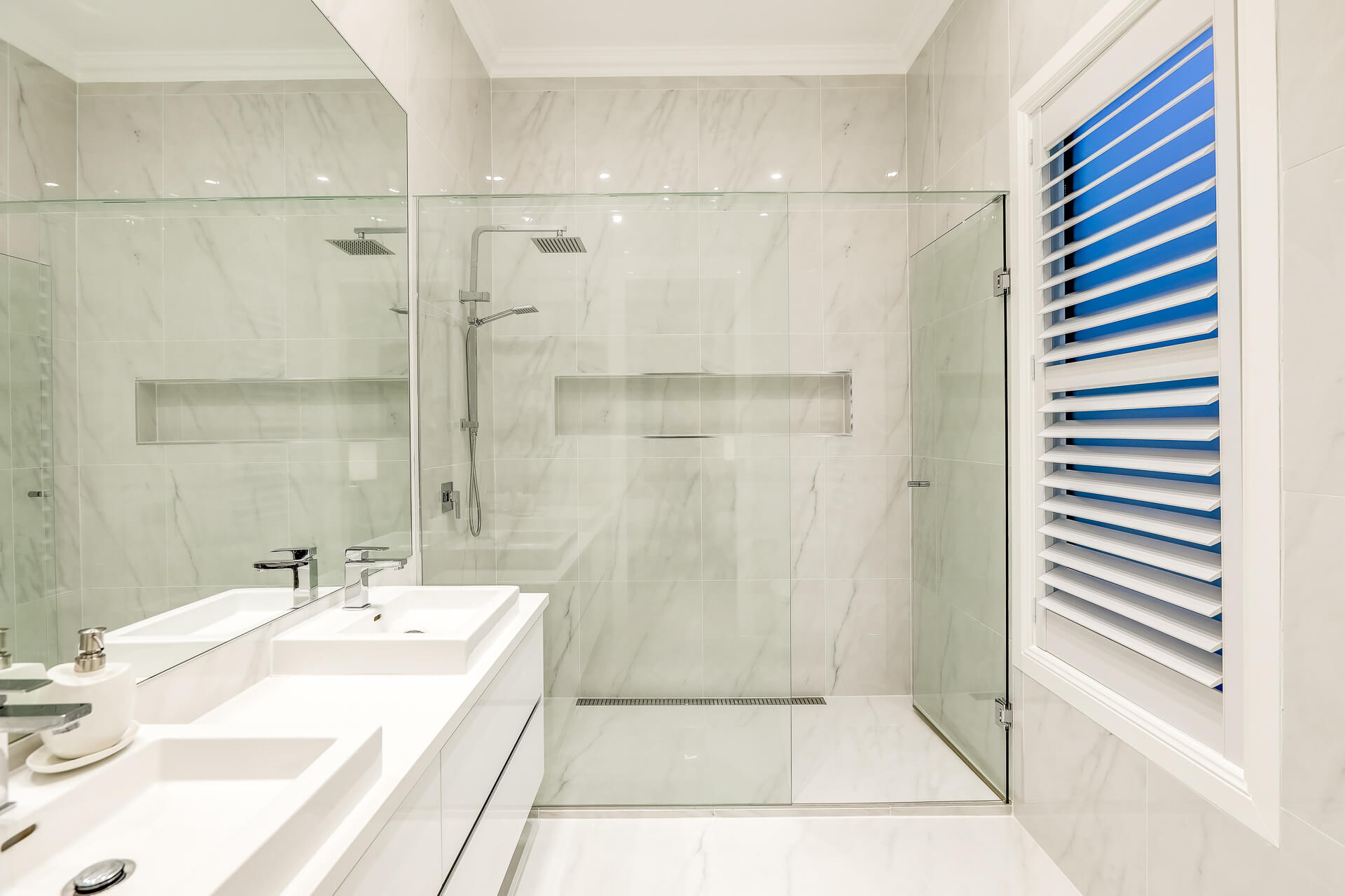 Bathroom with marbled tiles and shutters