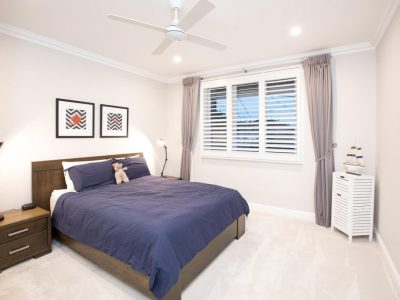 Bedroom with timber bed frame and shutters