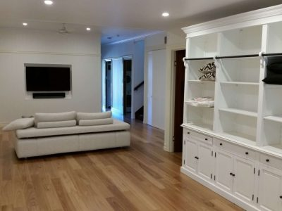 White storage, lounge and timber floor