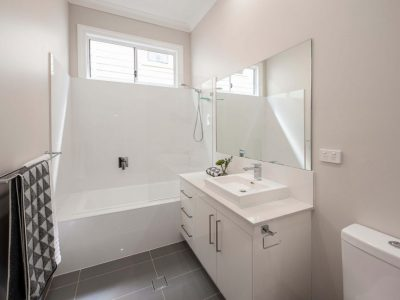 White bathroom with grey tiles and bath and shower