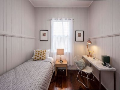 Single bedroom with white timber walls